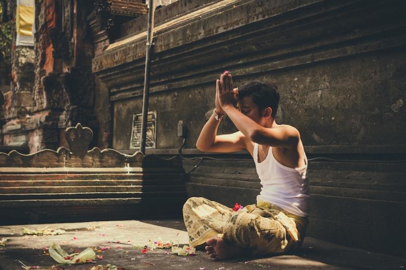 BALI, INDONESIA - DECEMBER 5, 2017: Balinese man praying in Tirta Empul Temple.